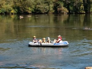Small raft with 2 adults and two kids in it. Oars on one side being handled by dad.